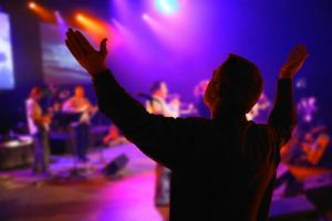 Man Worshipping as Religious Band Plays